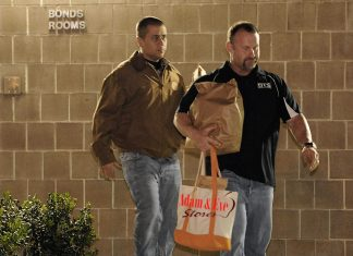 """George Zimmerman seen here walking out with his signature Adam & Eve bag filled with """"toys"""""""