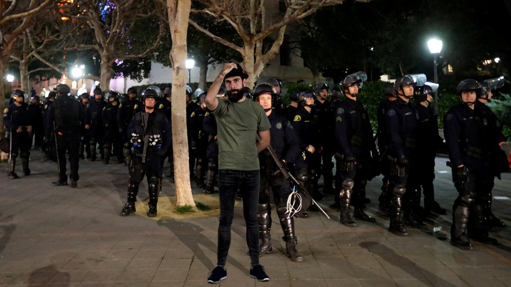 """elf-proclaimed postmodern social justice warrior David """"Riddle Me"""" Shoreston seen here trying to disrupt fascist police officers with his trademark skinny jeans and fedora."""
