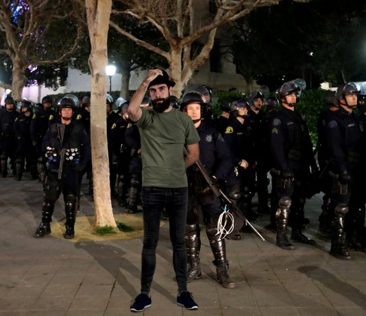 "elf-proclaimed postmodern social justice warrior David ""Riddle Me"" Shoreston seen here trying to disrupt fascist police officers with his trademark skinny jeans and fedora."